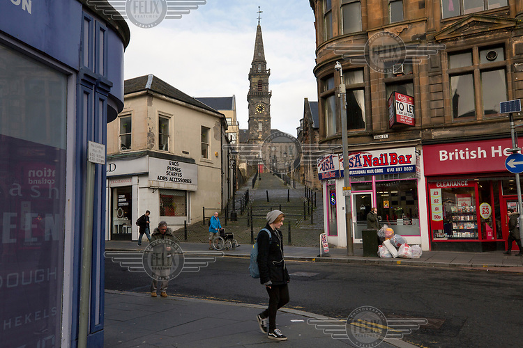 Paisley's high street (looking toward the iconic Oakshaw Trinity Church) hosts many empty and second-hand shops reflecting the town's economic decline.