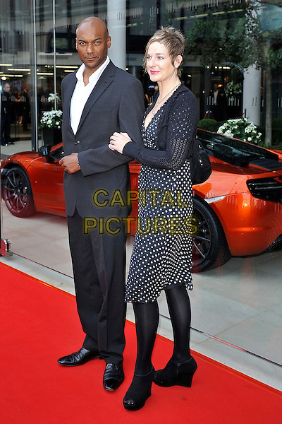 Colin Salmon & Fiona Hawthorne.attending the McLaren Car Showroom Launch at One Hyde Park, Knightsbridge, London, England, UK, June 21st 2011..full length grey gray suit white shirt husband couple wife polka dot  dress shrug  wedges ankle boots .CAP/MAR.© Martin Harris/Capital Pictures.