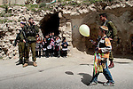 Israeli soldiers stand guard in front of Palestinian school girls as a Jewish settler (front) wearing costumes  takes part in a parade for the Jewish holiday of Purim in the West Bank city of Hebron March 20, 2011. Purim is a celebration of the Jews' salvation from genocide in ancient Persia, as recounted in the Book of Esther.Photo (C) Quique Kierszenbaum