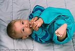 5 month old baby girl full length, on back, biting foot horizontal