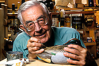 Senior man painting a hand carved duck decoy.
