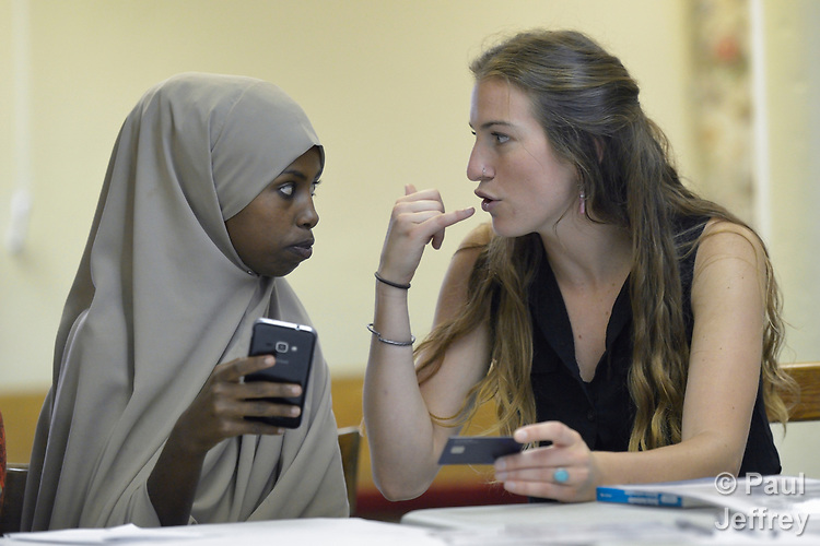 In the basement of a United Methodist Church in Durham, North Carolina, Julia Hause teaches a class in financial literacy for refugees, including Shukri Ahmed Omar, a newly arrived Somali refugee. They are practicing what to say when you call your bank to find out the balance on your debit card. Hause works for Church World Service, which resettles refugees in North Carolina and elsewhere in the United States.<br /> <br /> Photo by Paul Jeffrey for Church World Service.