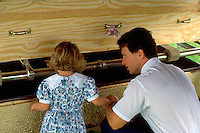Father and daughter ages 35 and 5 at grave looking into grandmas hand made plywood coffin.  Cambria  Wisconsin USA