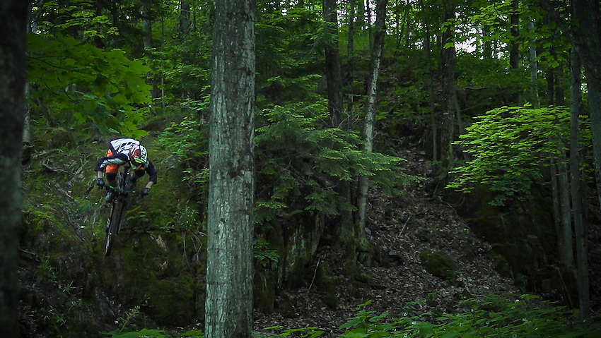 Still frame from Video: Mountain biker on rock roll feature on the trail called Your Mom in the Benson Grade freeride area of Marquette, Michigan.