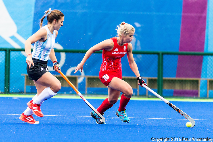 Sophie Bray #19 of Great Britain protects the baal from Carla Rebecchi #11 of Argentina during Argentina vs Great Britain in women's Pool B game  at the Rio 2016 Olympics at the Olympic Hockey Centre in Rio de Janeiro, Brazil.