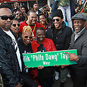 "Manager Rasta Root, A Tribe Called Quest member Jarobi White left and Q-Tip second from the right along with Mom Taylor, Deisha Taylor, Dad Taylor, Busta Rhymes and City Council Member Daneek Miller pose with the street sign at the Malik ""Phiwe Dawg"" Taylor Street Unveiled in Saint Albans, Queens on Saturday, Nov. 19, 2016 in New York. ( Donald Traill/ AP Photo)"