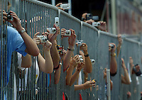 Nextel Cup fans squeeze their hands and their cameras through barriers to get a shot of the car of their favorite driver as they pass by for the pre-race inspection Saturday afternoon, July 3, 2004 at the Daytona International Speedway in Daytona Beach.(Kelly Jordan)