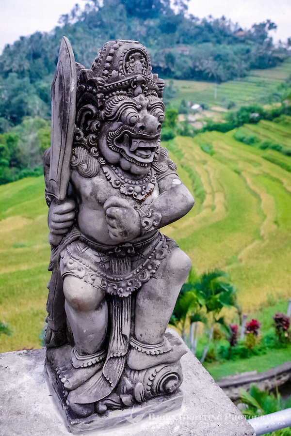 Bali, Karangasem, Besakih. Bali, Karangasem, Besakih. A small statue along the road to Besakih. Rice fields in the background.
