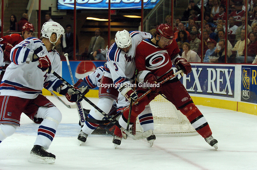 Carolina Hurricanes' Justin Williams, in red, battles for position with the New York Rangers' Michal Rozsival (3) and Martin Straka, left, Tuesday, March 14, 2006 at the RBC Center in Raleigh, NC. Carolina won 5-3.