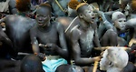 Dinka youth from a cattle camp near Akot, South Sudan sing and beat their sticks together in time to the music.  Hair died orange with cow urine, the youth have also smeared cow dung ash (the white marks) on their faces, heads, and bodies as a beauty cosmetic.  The cow dung ash has dual appeal, also actingas a mosquito repellent at night.
