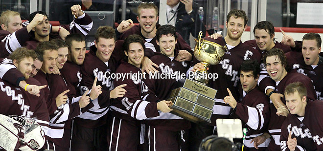 Colgate players celebrate with the Omaha Cup after defeating Nebraska Omaha 4-3 to win the Maverick Stampede. (Photo by Michelle Bishop)