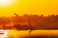 Luxor, Egypt. The sun sets over the Nile. A felucca seen from the East Bank.
