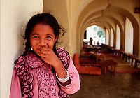 Portrait of a giggling young Indian girl standing outside of a mosque. Srirang, India.