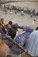 Spectators, some armed, prepare to leave at the end of another day's sport at the Twic Olympics in Wunrok, Southern Sudan.