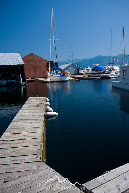 Idaho, North. Lake Pend Oreille, Bayview. An empty boat slip reflects the distant moored sailboat on Scenic Bay.