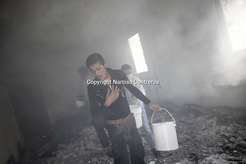 Syrian civilians try to put out the fire caused by a Syrian aircraft shelling as it targets a house building killing many civilians and injuring many others at the residential neighborhood of Zahraa in northeastern Aleppo. The Syrian army is carrying out aircraft shellings over residential areas throughout Aleppo City killing hundreds of civilians during the ongoing battle for the control of the city.