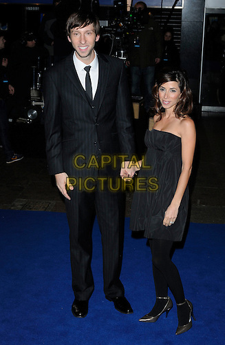 """JOEL DAVID MOORE & KAREN MOORE.At the World film premiere of """"Avatar"""", Odeon cinema Leicester Square, London, England, UK, .10th December 2009..arrivals full length black suit tie strapless dress tights holding hands couple married husband wife gold ankle strap shoes pinstripe.CAP/CAN.©Can Nguyen/Capital Pictures"""