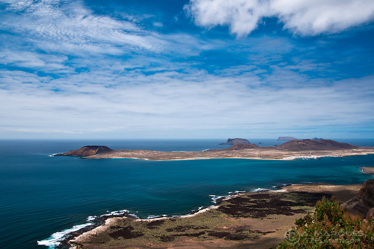 Isla Graciosa as seen from Lanzarote, Canary Islands, Spain. The Graciosa island, across from the El Rio strait, is the smallest inhabited Canary Island with around 700 inhabitants. It is part of the Chinijo Archipelago National Park, and cars are forbidden on the island. Just behind it the 2.7 square kilometer islet of Montana Clara, an important fauna spot, and behind that can be seen the northenmost island of the Canaries, Alegranza.