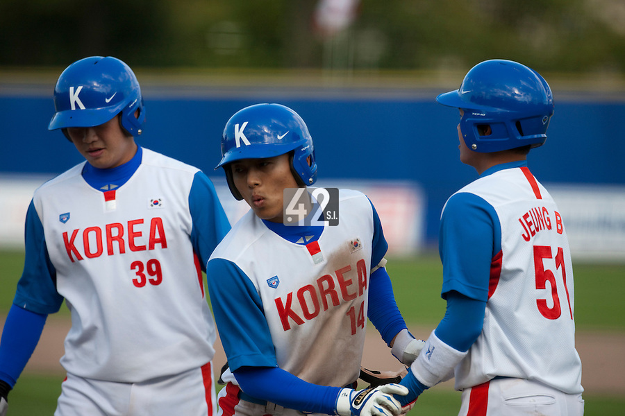 14 September 2009: Left fielder Hun-Gon Kim of South Korea is congratulated by #39 Hee-Keun Lee and #51 Boung-Gon Jeung as he hits an homerun during the 2009 Baseball World Cup Group F second round match game won 15-5 by South Korea over Great Britain, in the Dutch city of Amsterdan, Netherlands.