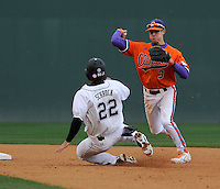 Shortstop Tyler Krieger (3) of the Clemson Tigers makes the putout on Max Schrock (22) of the South Carolina Gamecocks and throws to first in the eighth inning on Saturday, March 2, 2013, at Fluor Field at the West End in Greenville, South Carolina. Clemson won the Reedy Rivalry Game, 6-3. (Tom Priddy/Four Seam Images)