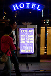 A couple walks past a sign advertising short stays from 3,600 yen outside a love hotel in the Dogenzaka entertainment district -- sometimes referred to as Love Hotel Hill -- in Tokyo, Japan on Sunday 19 April  2009. .Photographer: Robert Gilhooly