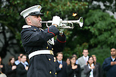 """Washington, DC - September 11, 2009 -- A bugler plays """"Taps"""" as United States President Barack Obama and first lady Michelle Obama stood for a moment of silence at 8:46am in honor of those lost during the terrorist attacks on September 11th, 2001.  Members of the White House staff were on hand for the event that was held on the South Lawn of the White House.  .Credit: Gary Fabiano - Pool via CNP"""