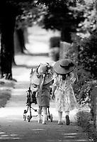 Little girls in hats pushing stroller.