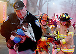 South Windsor animal control officer Brian Kelley and firefighters Alison Sheldon and Sarah Cooney, rush two of the three cats rescued from a house fire to Kelley's vehicle to bring them to a veterinarian, Tuesday, January 8, 2019, in South Windsor. The fire came in around 4pm at 234 Long Hill Road when a passing motorist noticed smoke coming from the house. Three dogs escaped when police arrived and opened a door. The three cats were removed by firefighters, 2 responded quickly to the oxygen they were given a third seemed to be unconscious as firefighters continued to work on him. The house sustained heavy damage to the kitchen and living room, the area around a wood stove sustained the heaviest damage, Chief Kevin Cooney said. The house was deemed uninhabitable and the residents are staying with other family members Cooney said. (Jim Michaud / Journal Inquirer)