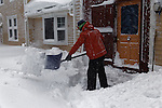 Young man shoveling snow, Camden, Maine, USA