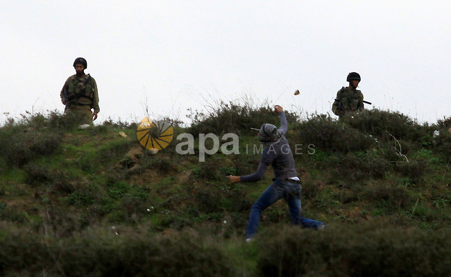 A masked Palestinian throws stones during clashes with Jewish settlers, not pictured, outside the West Bank village of Madama and the Jewish settlement of Yitzhar, near Nablus, Dec. 17, 2012. Photo by Nedal Eshtayah