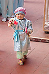 Vietnamese female child in dressed in traditional costume for ceremony at Buddhist temple twirls musical instrument in her hand