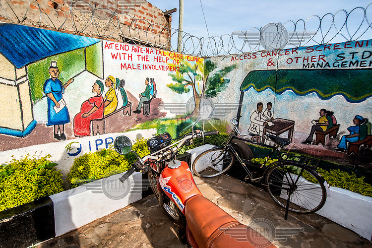 Staff vehicles parked in front of educational murals at the RHU (Reproductive Health Uganda) clinic.
