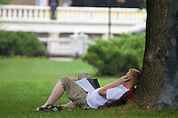 Man lying on the green lawn reading magazine in Alexander Garden, Moscow, near the Kremlin wall