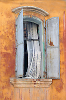 Metallic shutters adorn this window with lace on its ledge in Avayalik, Turkey