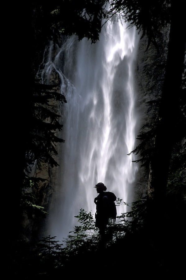 Silhouette of hiker against waterfall, Comet Falls Trail, Mt Rainier National Park, Washington