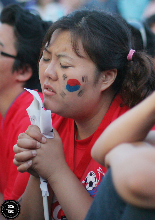 An South Korean National Soccer Team fan at the Fan Festival in downtown Leipzig, Germany is immersed in a prayer after South Korea falls behind France 1-0 in Korea's FIFA World Cup first round match against France on Sunday, June 18th, 2006.  The game ended in a draw 1-1.