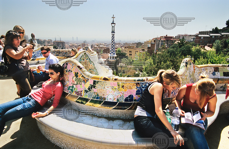 Girls reading in Parc Guell. The park was designed by Antoni Gaudi and built in the years 1900 to 1914. Its focal point is the main terrace, surrounded by a long mosaic bench in the form of a sea serpent.