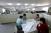 Japanese and Chinese engineers attend a meeting in the temporary offices of Oji Paper Factory, in Nantong, Jiangsu province, China, on May 25, 2010. Photo by Lucas Schifres/Pictobank