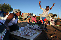 A boy jumps joyfully next to a woman selling chicken feet and entrails in a township on the outskirts of Johannesburg, South Africa.   Julia Cumes/Zuma