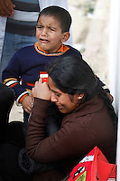 Sudha Sirakumar from Sri Lanka, with her son Darshan (3), cries as she sits down just inside the Tunisian border..Tens of thousands of people, mainly Egyptian workers, flee unrest in Libya and cross the border into Tunisia. Some slept in the open for several days before being processed.  At the same time forces loyal to Col. Gaddafi fought opposition forces in various parts of the country.