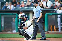 Roberto Pena (31) of the Salt Lake Bees and umpire Lewis Williams handles the calls behind the plate during the game between the Salt Lake Bees and the Round Rock Express at Smith's Ballpark on June 10, 2019 in Salt Lake City, Utah. The Bees defeated the Express 9-7. (Stephen Smith/Four Seam Images)