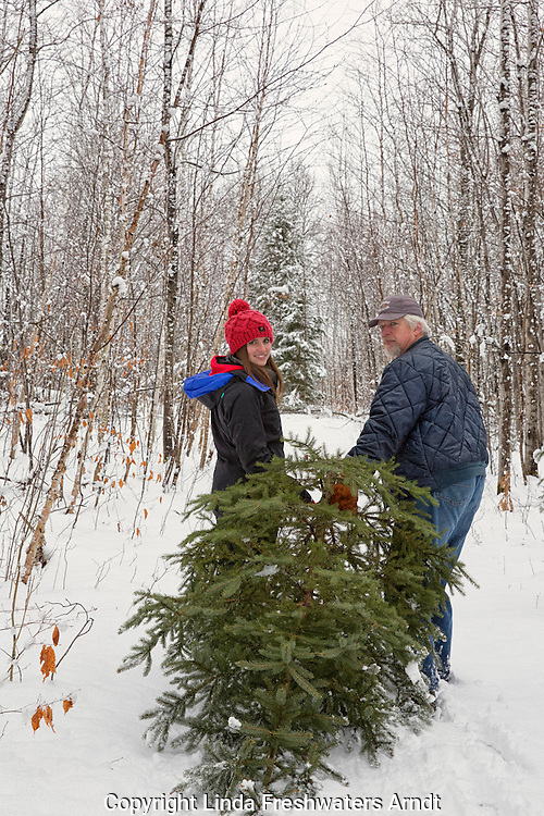 Father & daughter bringing a tree home to decorate for Christmas