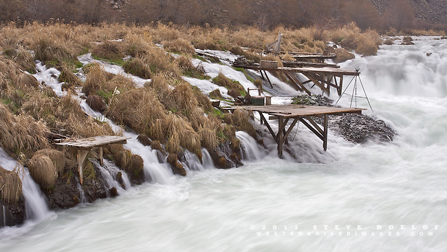 Tribal fishing platforms cling to the basalt outcrops along the Deshutes River at Sherar Falls.