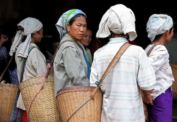 These women are waiting for rice to be distributed by a local NGO. But even with food donations, many children go hungry. A third of them suffer from malnutrition.<br /> <br /> Since early 2006, some 2,000 refugees have fled from Myanmar into Thailand. They join 140,000 previous arrivals, many of whom have been living in refugee camps in northern and western Thailand for as long as 20 years.