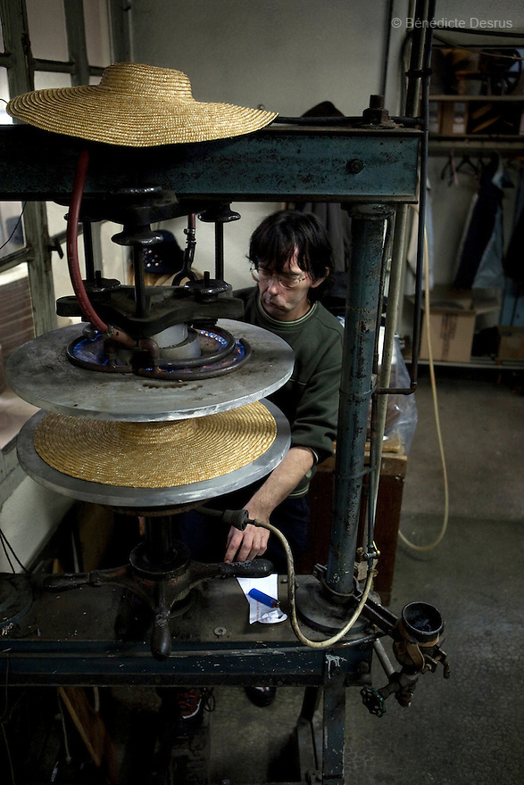 """9 december 2009 - Coustilleres' hat factory, Septfonds, France - Robert Cavaille works on the Plate Machine to press a hat. The model of the hat is called """"provencal""""..Septfonds is the heart of French straw hat making, due to its very ancient hatter tradition. The hat making industry had its commercial peak in the late 19th century..Coustillères is a family owned hat making factory that has been making straw hats in Septfonds for nearly 100 years. They make hats from straw, felt, and cloth as well as caps. The current owner is Jean-Claude Coustilleres. He is one of the last hat makers of the region..The straw hat making process is very labor intensive and numerous hands are involved. Nearly all of the equipment is over 100 years old, they use the original presses and tools including aluminium molds and sewing machines and dye their own straw continuing the traditional methods of manufacturing. The hat blocking and shaping, straw braids construction and dyeing are all done by hand..The company works on behalf of fashion houses and makes a variety of regional and historical hats. It produces 2 collections a year distributed by a network of salespeople and through a catalog to clients around the world. Photo credit: Benedicte Desrus"""