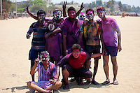 Indian boys celebrating annual Hindu Holi festival of colours with powder paints on beach by Marine Drive, Mumbai, India