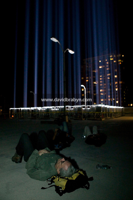 11 September 2005 - New York City, NY - A man observes a one-night installation shining beams of light up into the sky above Downtown Mahattan in New York City, USA, on 11 September 2005, the fourth annniversary of 9/11, as a tribute to victims of the terrorist attacks.