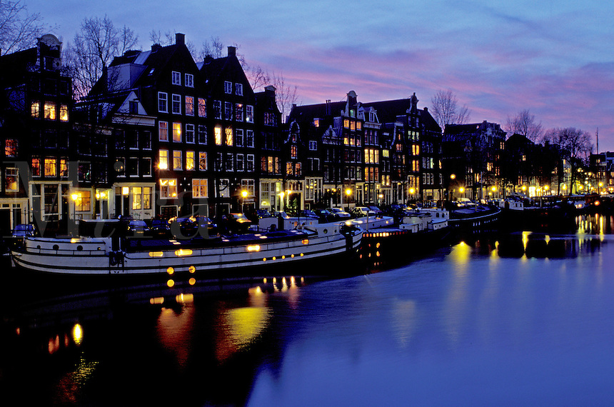 canal, Amsterdam, Holland, The Netherlands, Europe, Houses reflect in the calm waters of the canal (grachten) in downtown Amsterdam at night