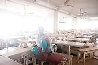 A Bangladesh garments worker sits inside the garments factory.  The garments workers start hunger strike for demanding their 3 months' salary and other benefits.  Dhaka, Bangladesh