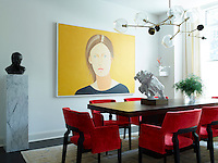 In the dining room, bold red armchairs by Caste upholstered in a Holly Hunt velvet, surround a circa 1960 dining table by Milo Baughman. The chandelier above is by Lindsey Adelman and the portrait painting is by Alex Katz. . A display of ferns in a glass vase and a sculpture by Rachel Feinstein stand on the table.
